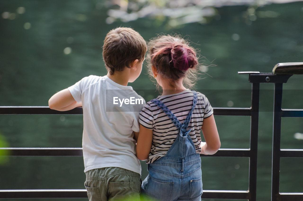 Rear View Of Siblings Standing By Railing Against Lake