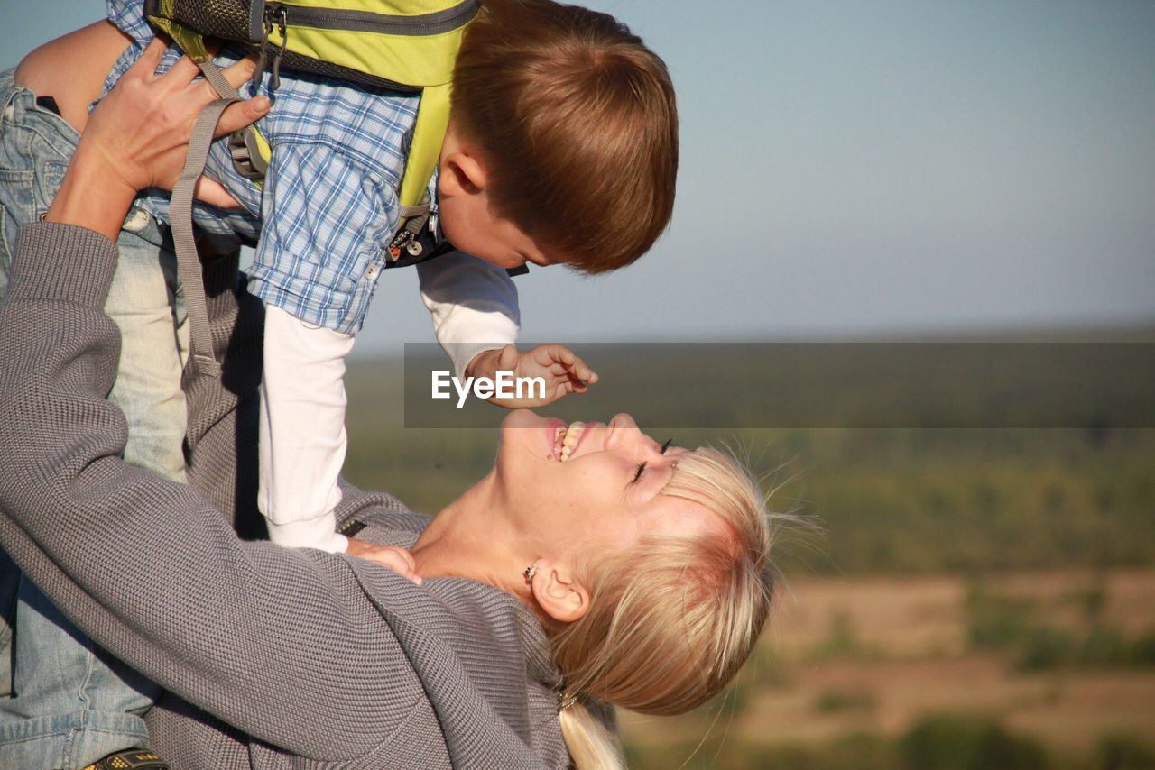 Side view of happy mother picking up son while standing on field against sky