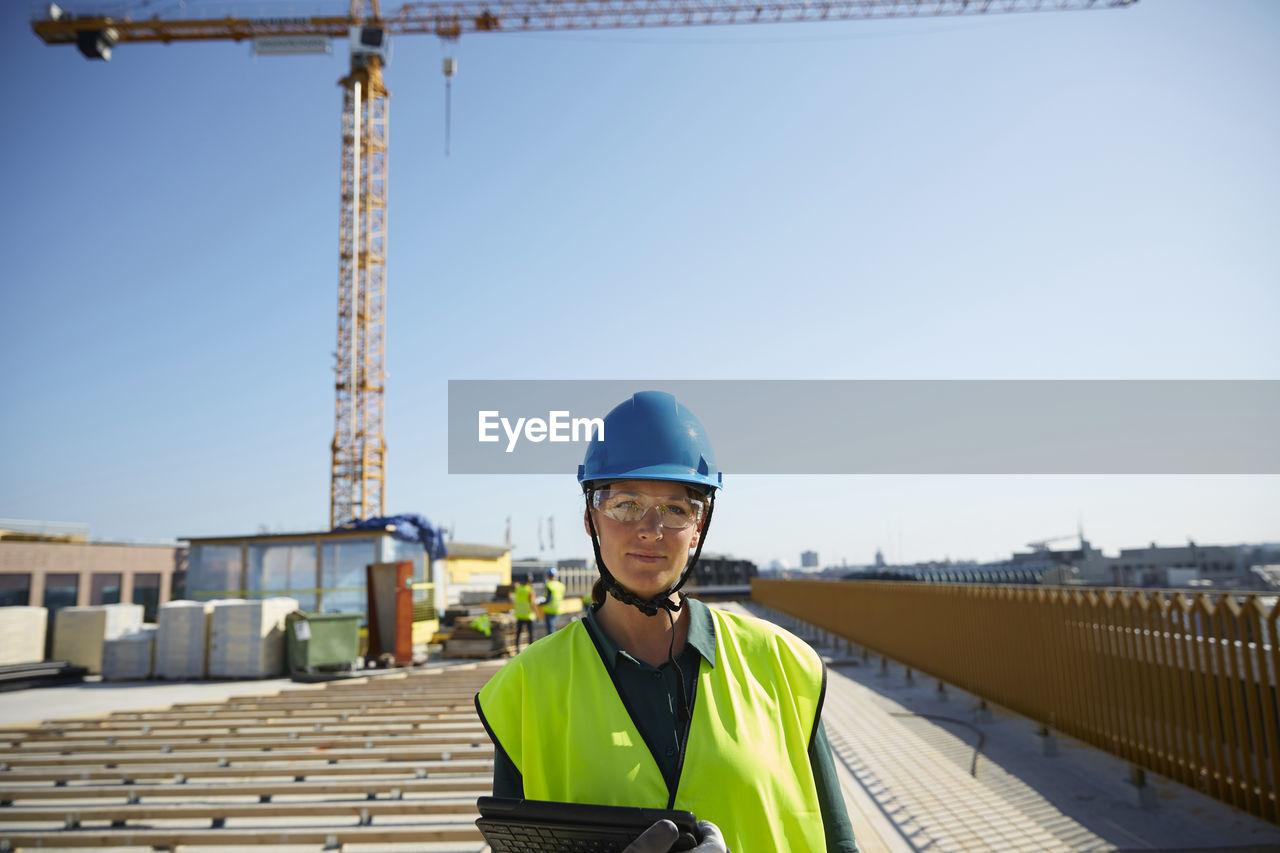 PORTRAIT OF SENIOR MAN AGAINST CONSTRUCTION SITE AGAINST SKY