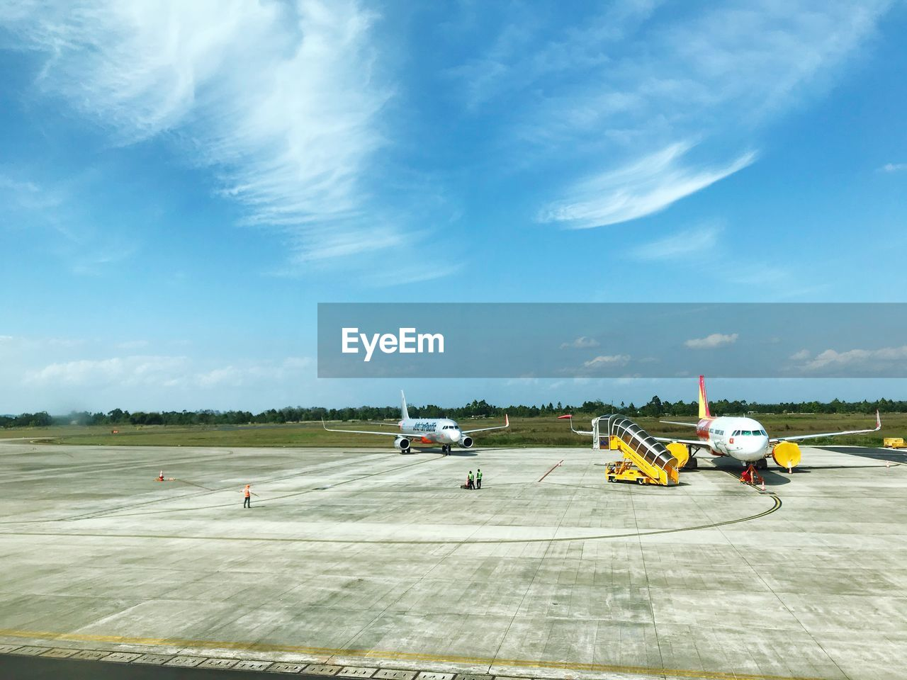 sky, air vehicle, transportation, airport, airplane, cloud - sky, airport runway, day, mode of transportation, group of people, real people, nature, outdoors, travel, road, sunlight, runway, cone, occupation, aerospace industry