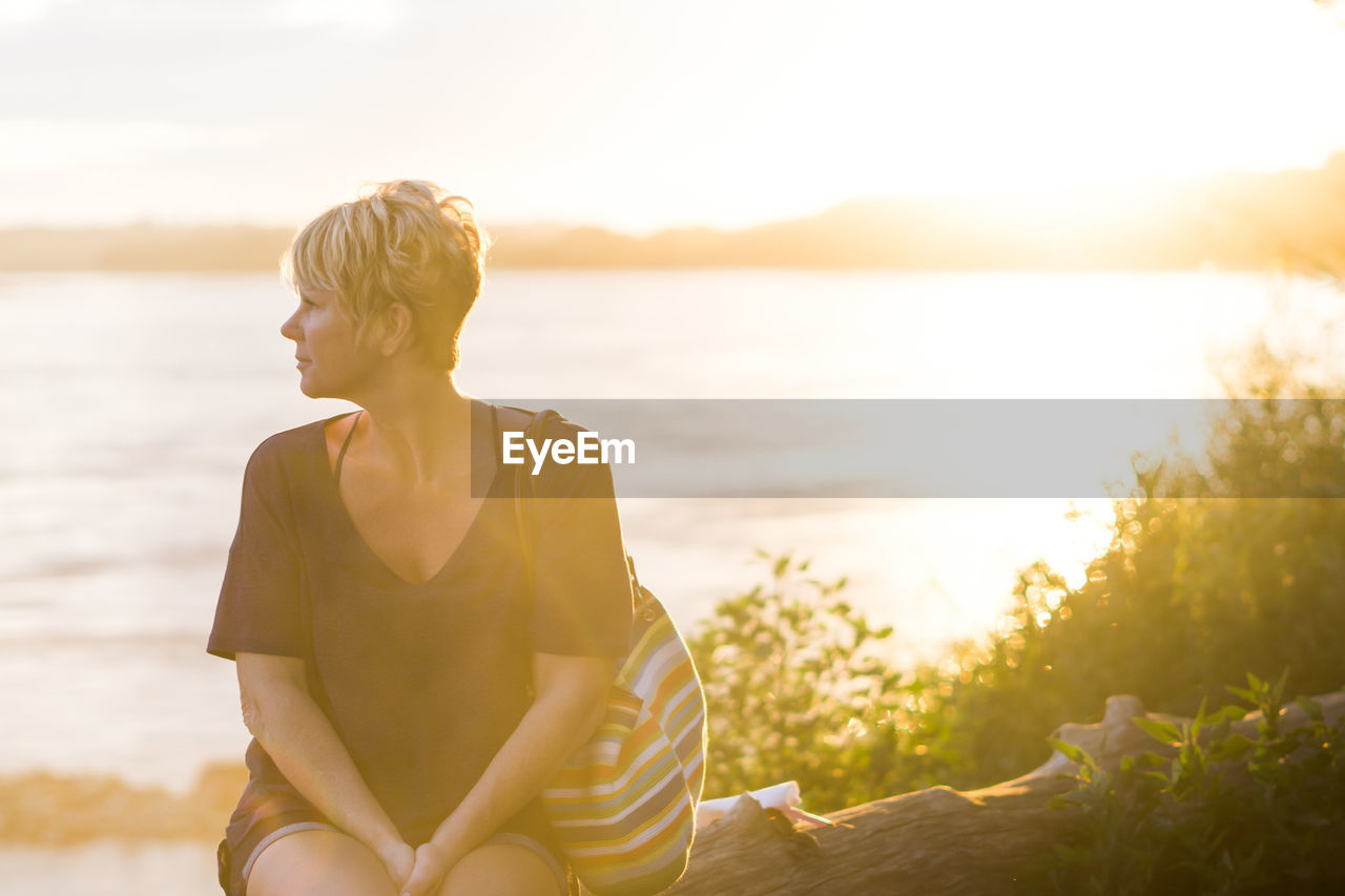 Woman Sitting On Trunktree On Sunset