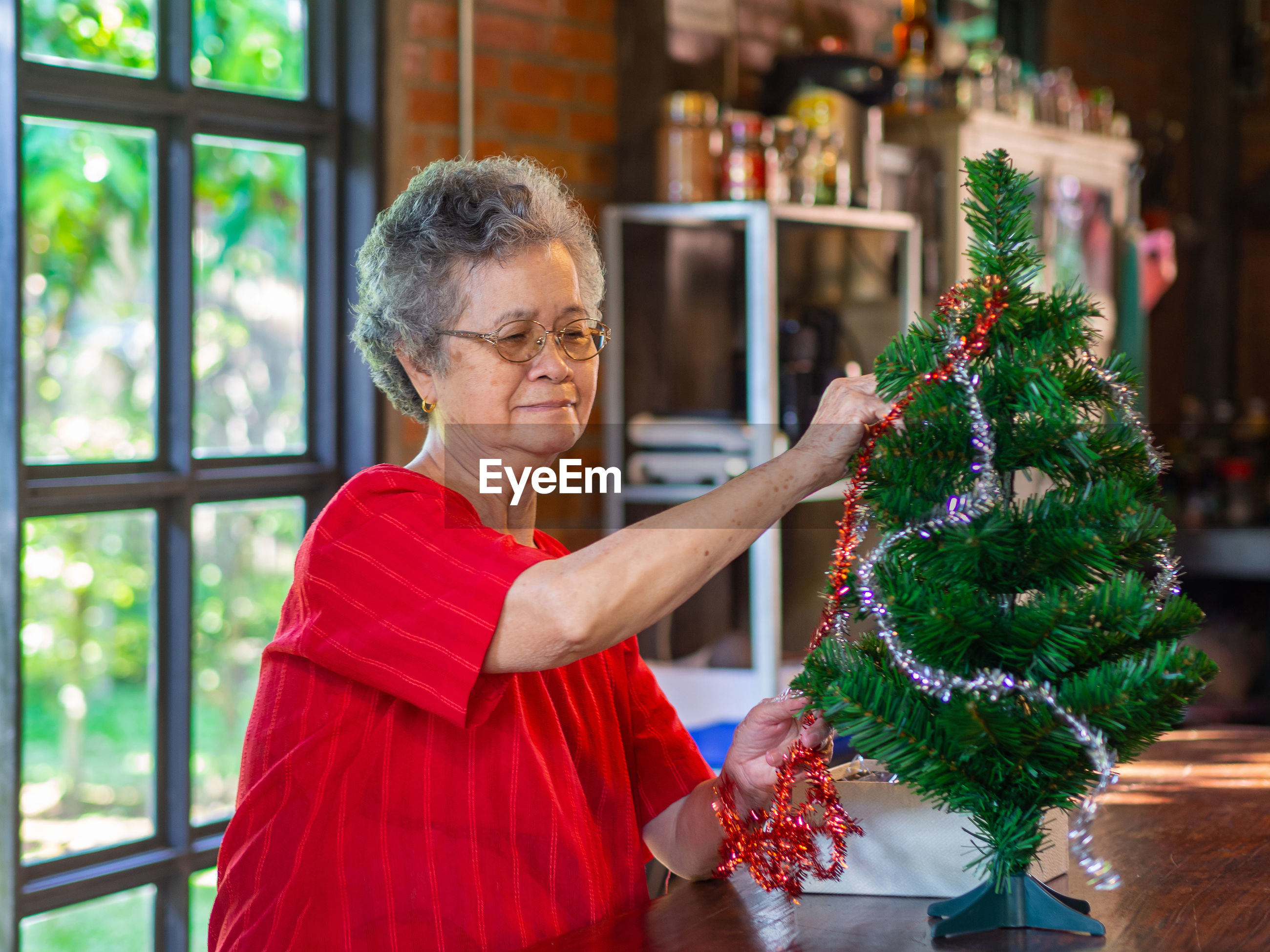 Senior woman decorating christmas tree at home