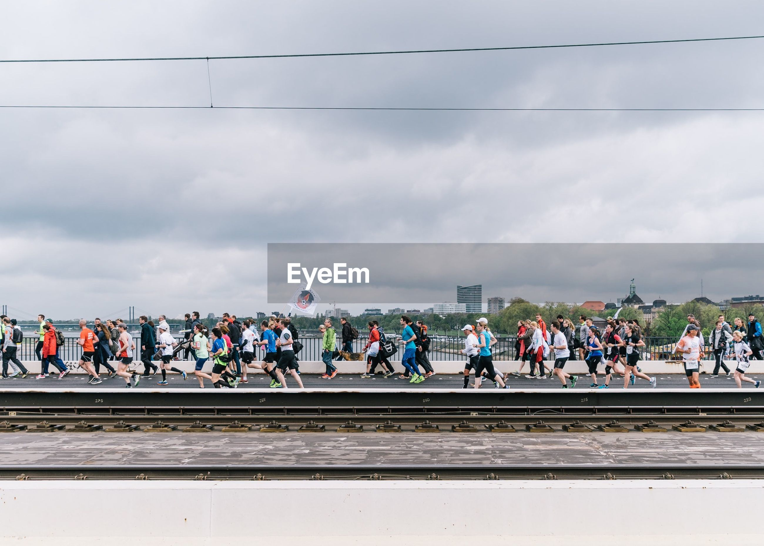 Athletes running on railway bridge during marathon