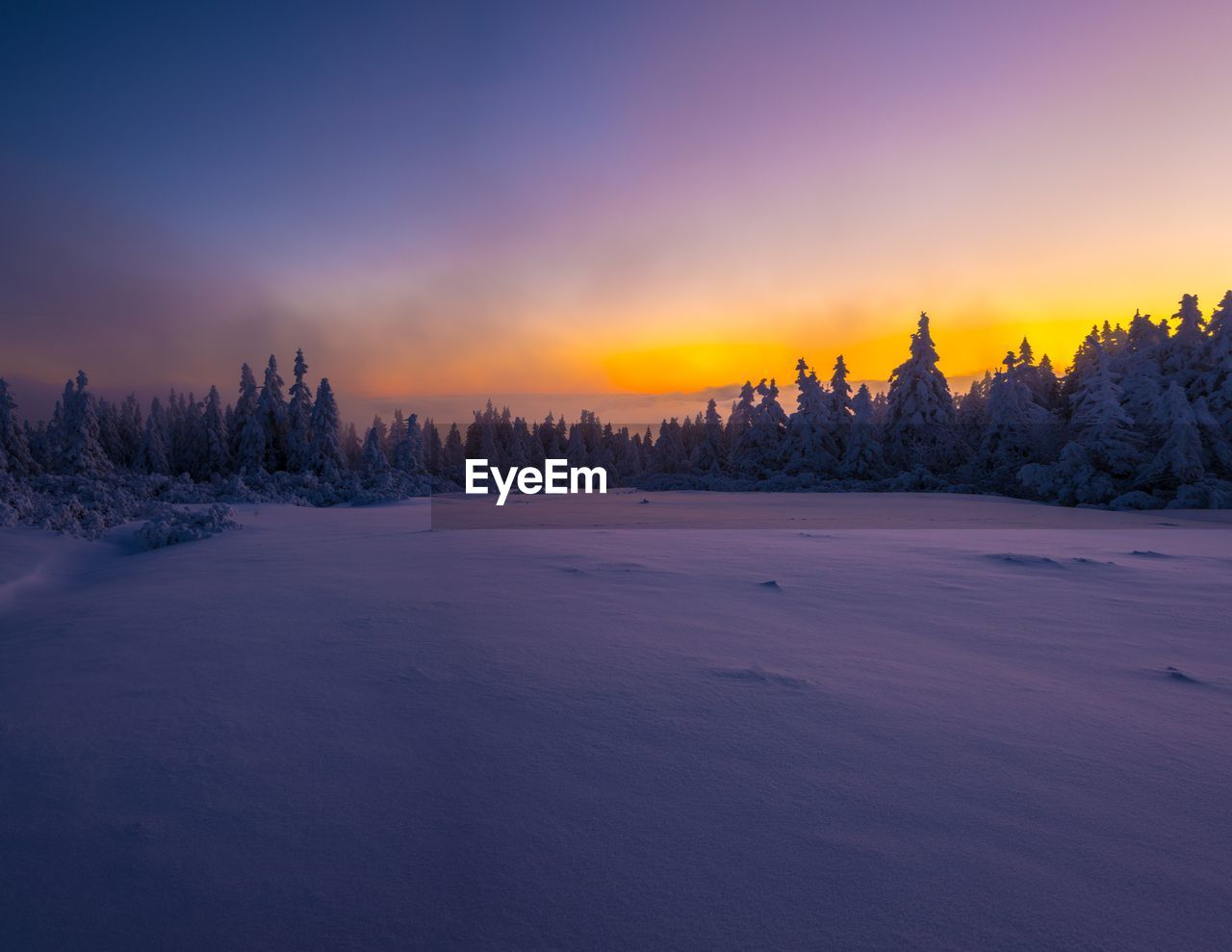 Idyllic view of snow covered field against sky during sunset