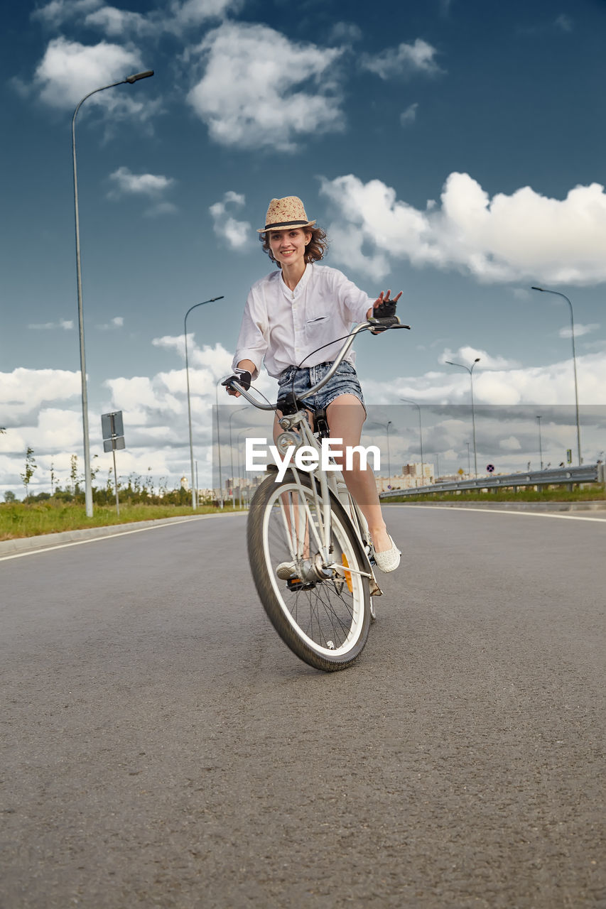 MAN RIDING BICYCLE BY ROAD AGAINST SKY