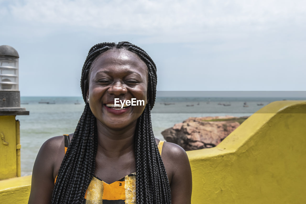 Happy africa woman from ghana stands on the coast in accra city.