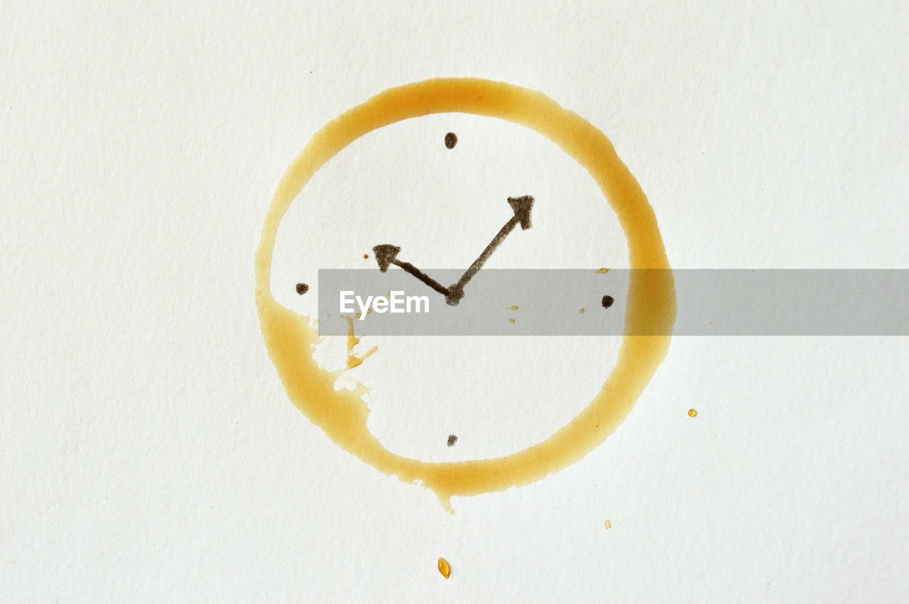 Close-up of clock face with coffee stain on white background