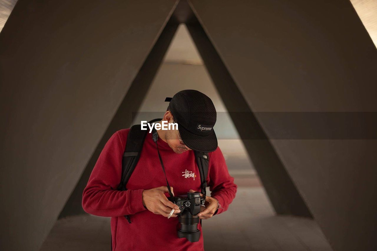 one person, camera - photographic equipment, standing, real people, technology, photography themes, lifestyles, indoors, front view, holding, young adult, photographing, photographic equipment, leisure activity, waist up, red, activity, wall - building feature, clothing, photographer, digital camera, obscured face