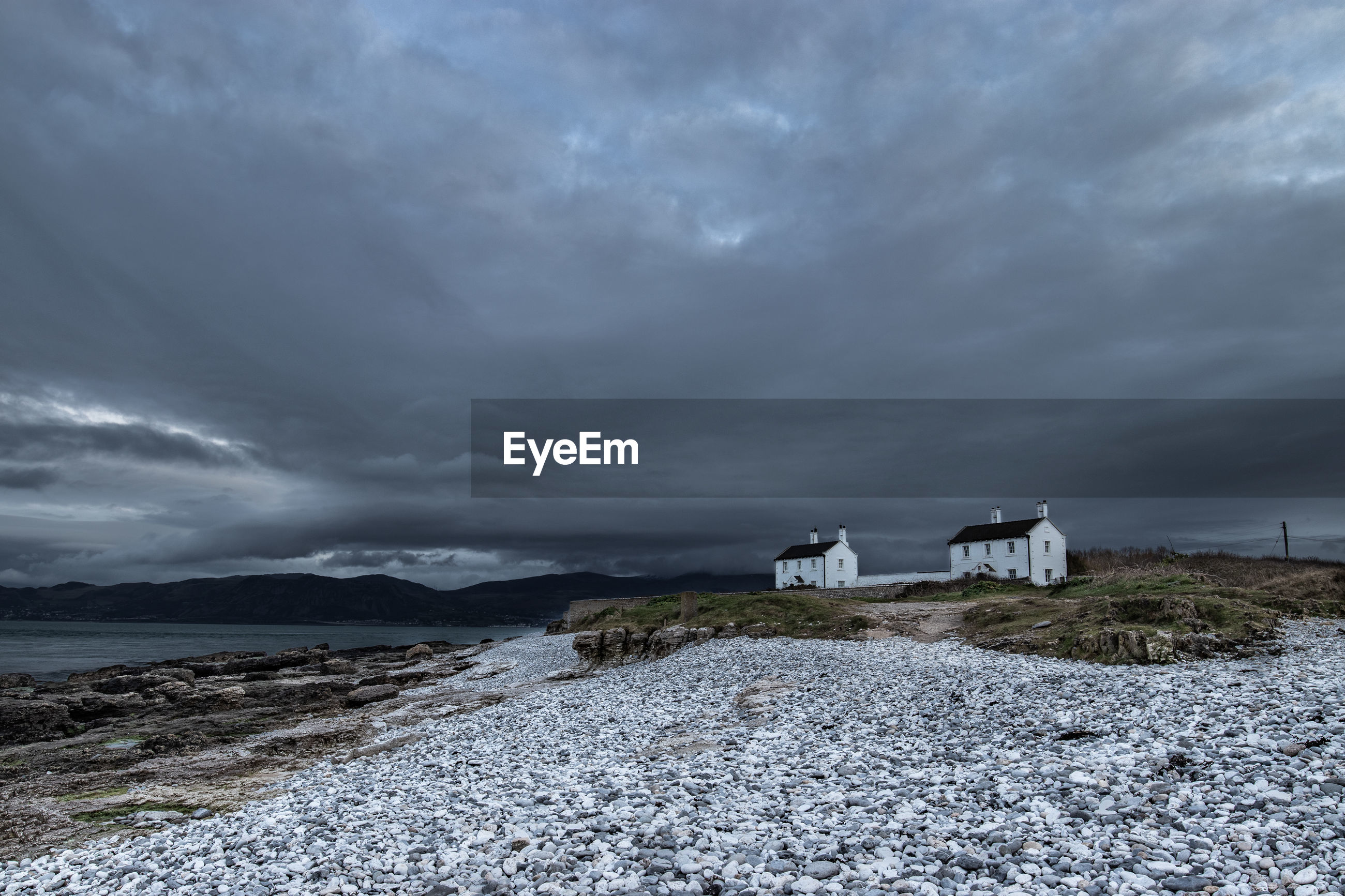 Cloudy sky at sunset over the two cottages at penmon point near the lighthouse