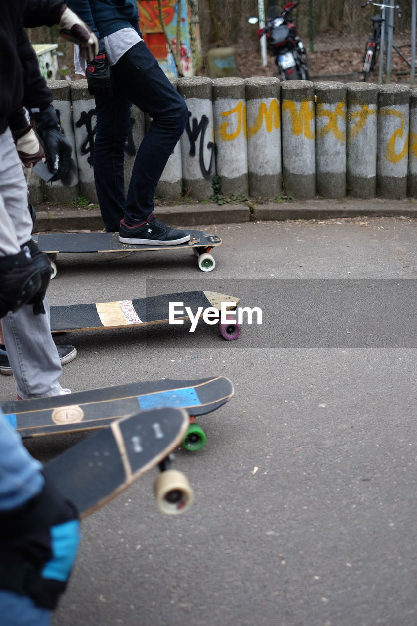 Low Section Of People Skateboarding At Park