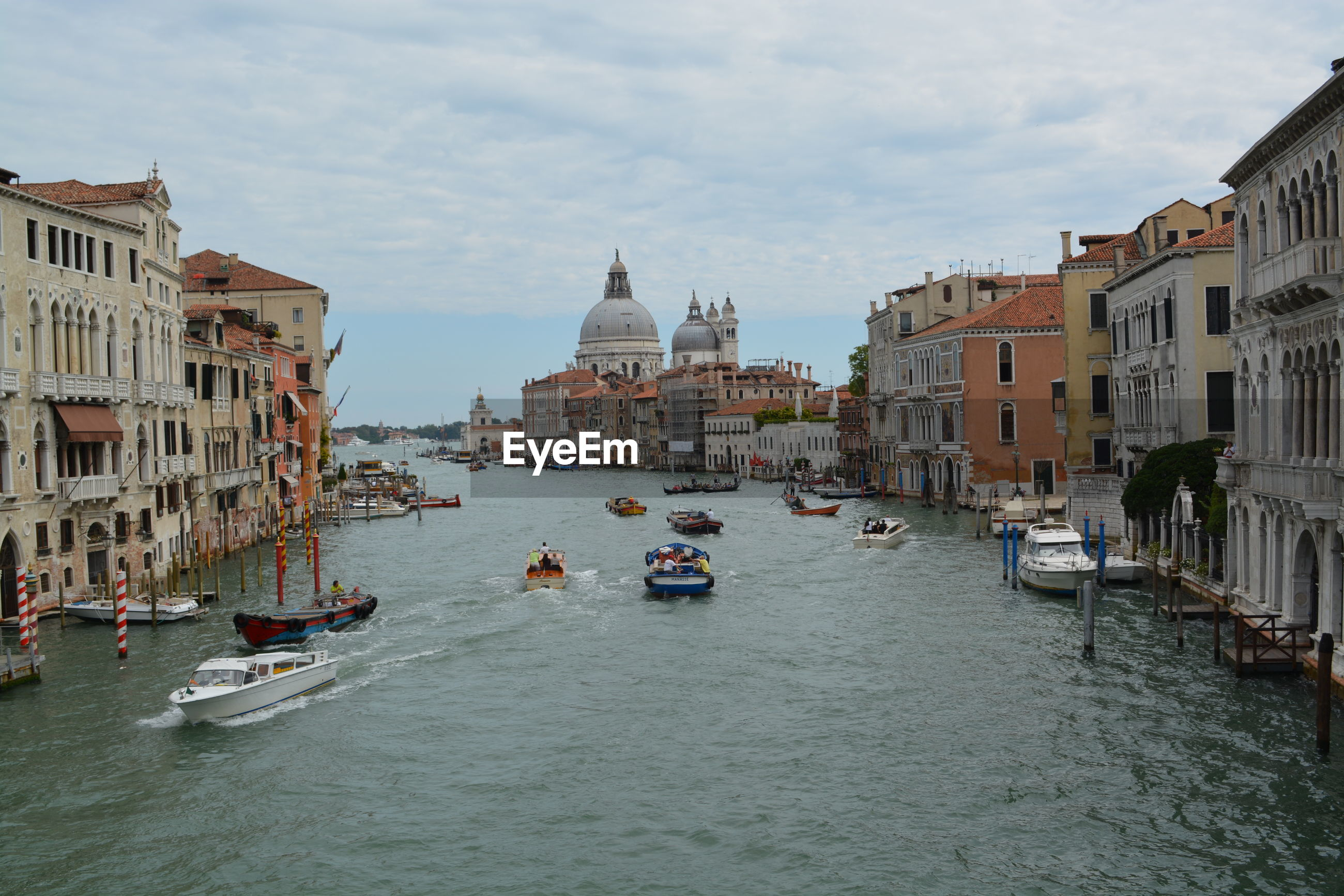Boats on grand canal amidst buildings in city