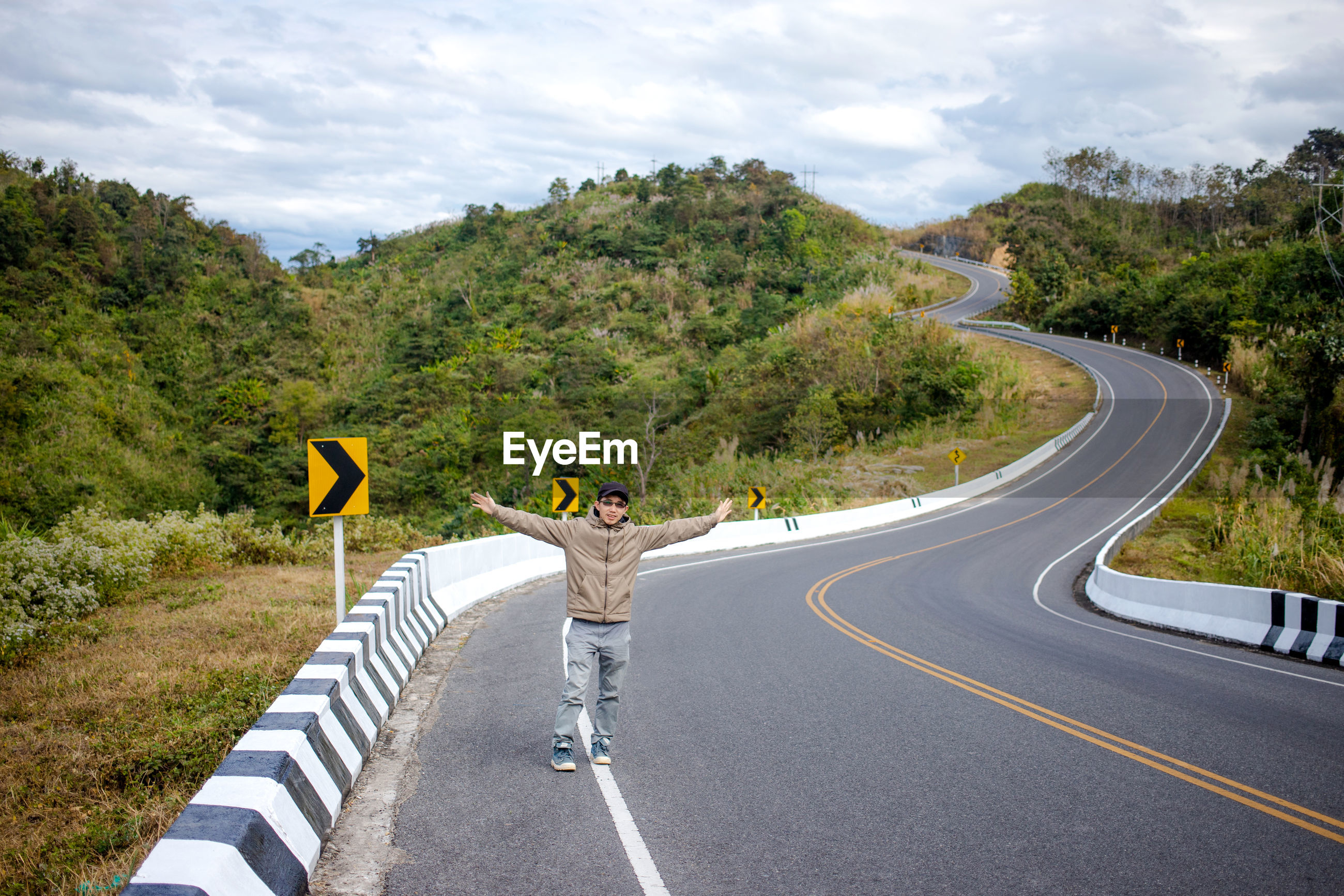 Full length of man with arms outstretched standing on country road