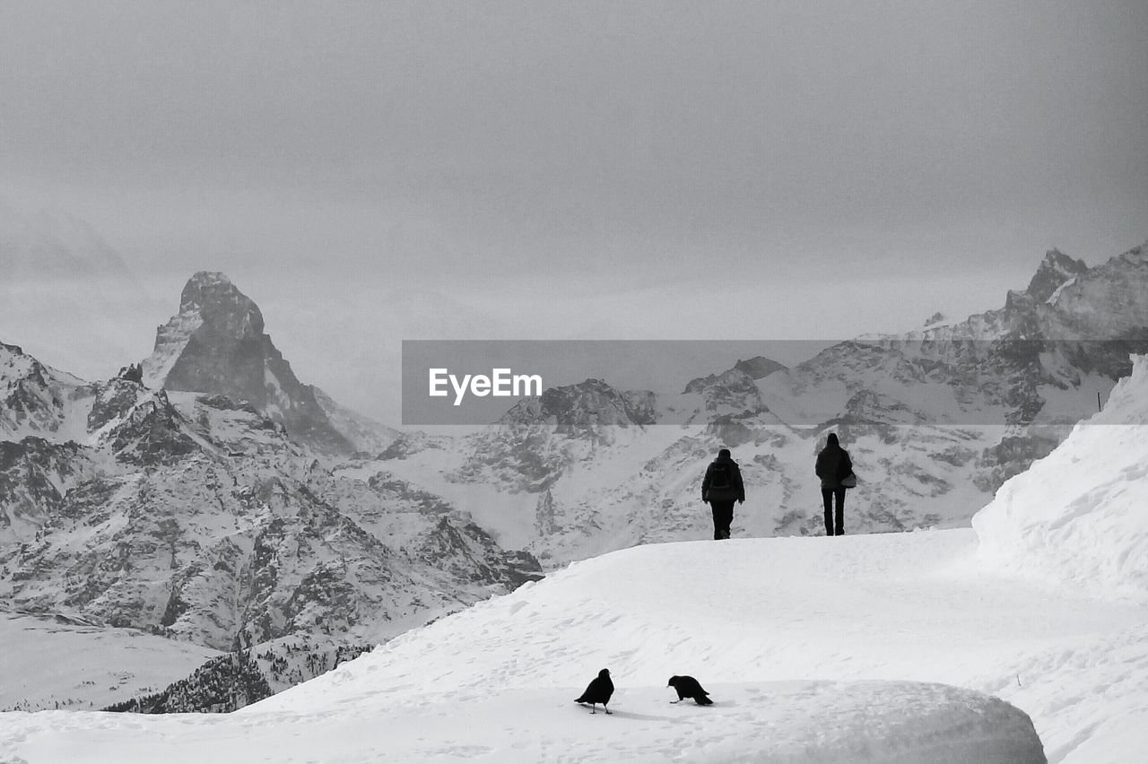 Silhouette people and birds on snowcapped mountain against sky