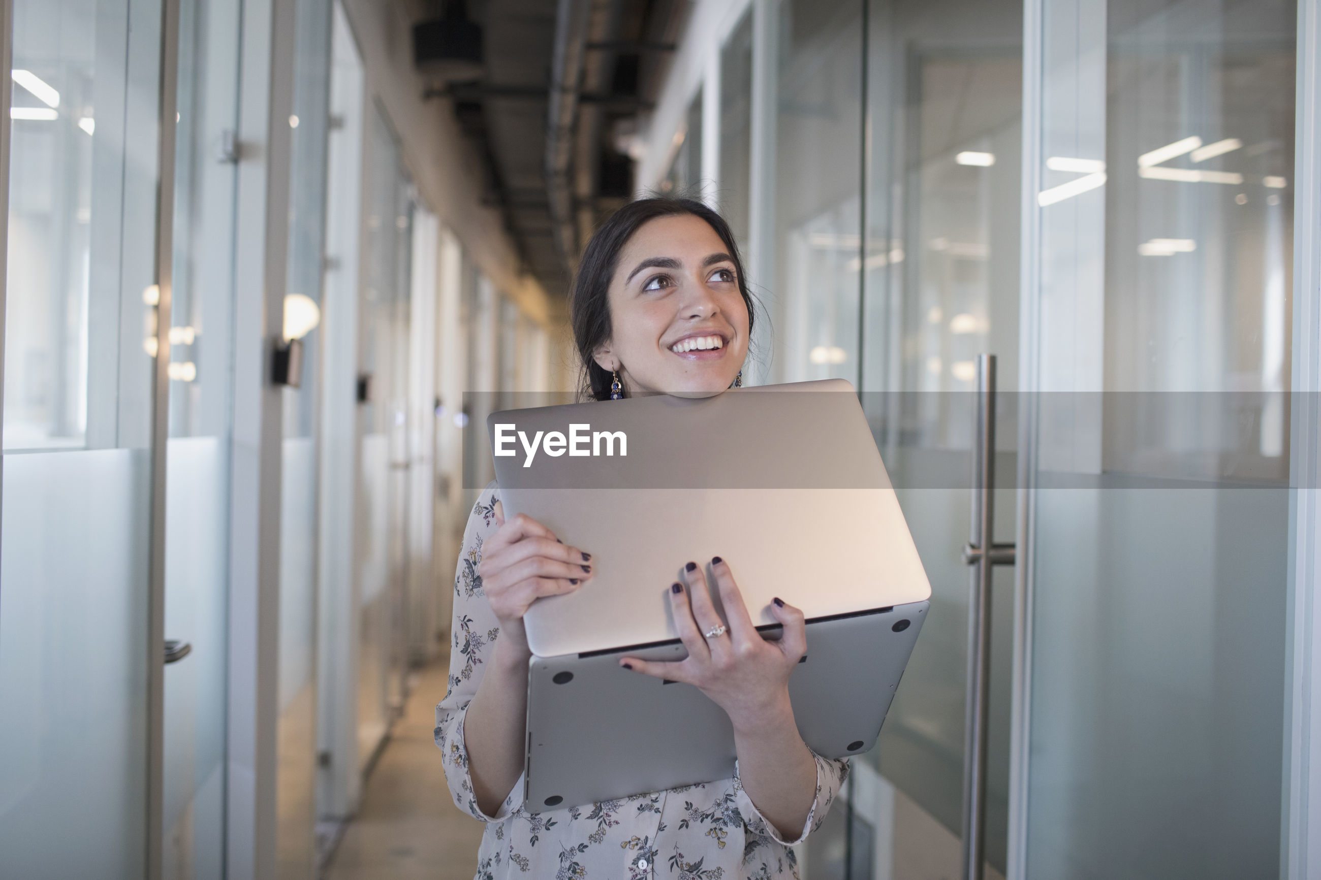 PORTRAIT OF A SMILING YOUNG WOMAN USING MOBILE PHONE IN CORRIDOR
