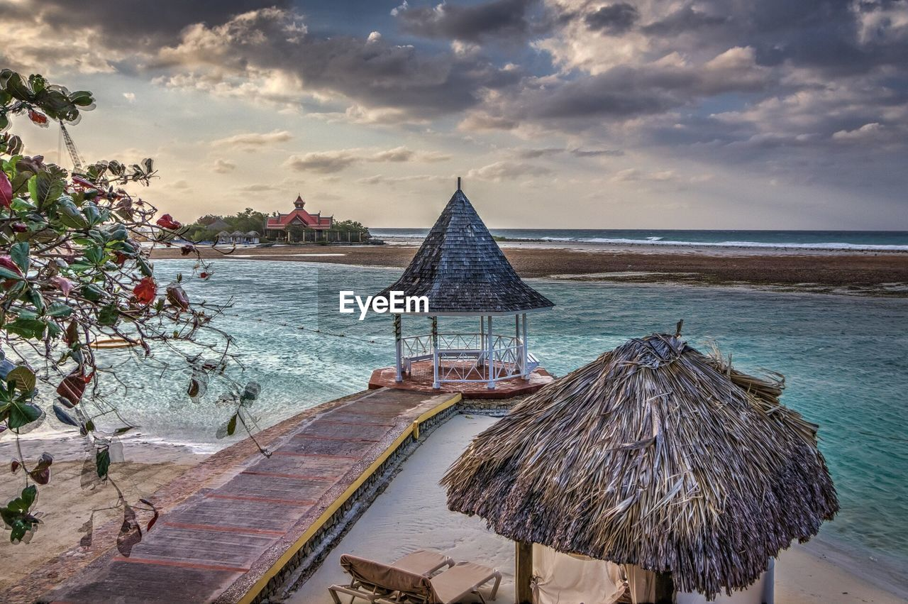 water, thatched roof, sea, cloud - sky, sky, nature, beach, tranquility, beauty in nature, horizon over water, scenics, shelter, outdoors, no people, day, tree