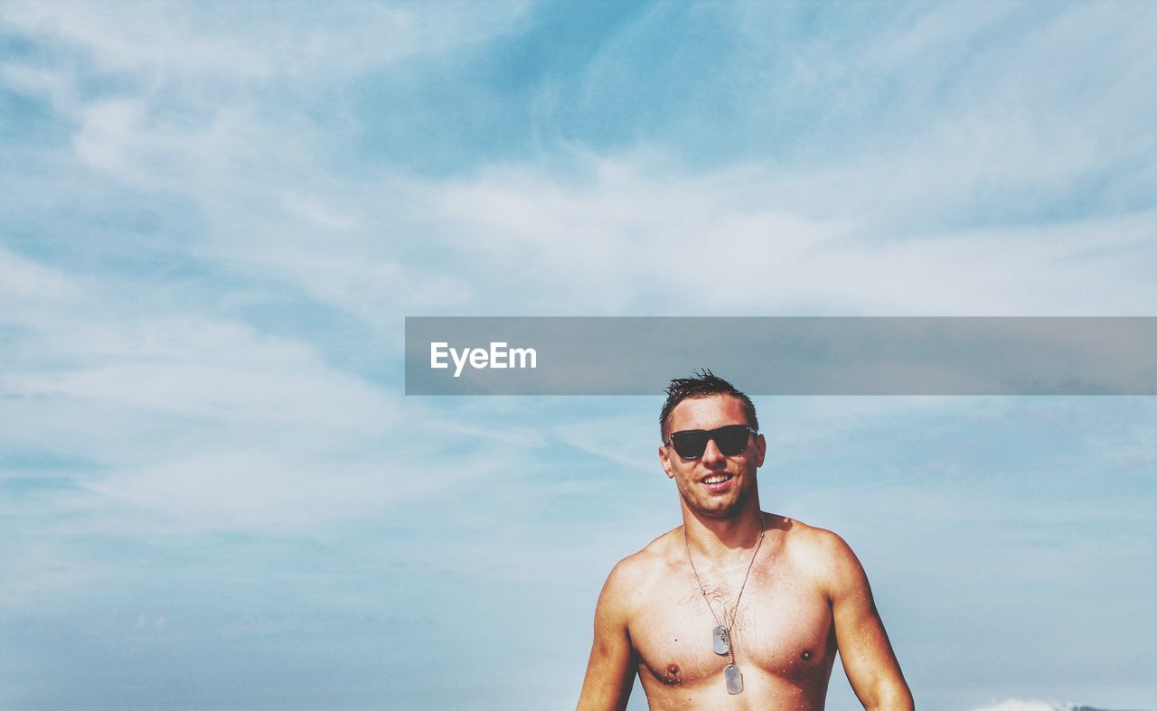Portrait of young man wearing sunglasses standing at beach