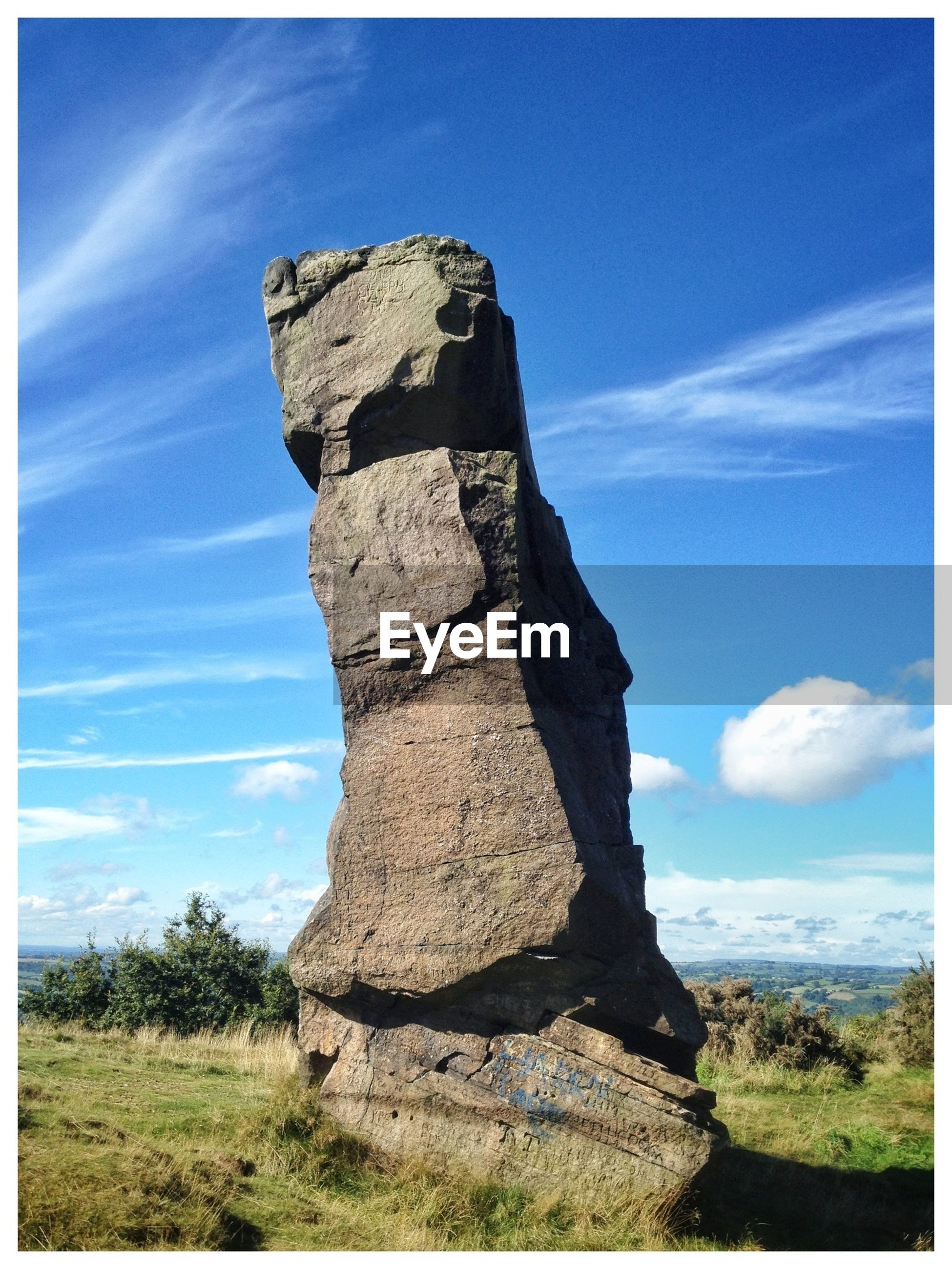 Stack rock on field against sky
