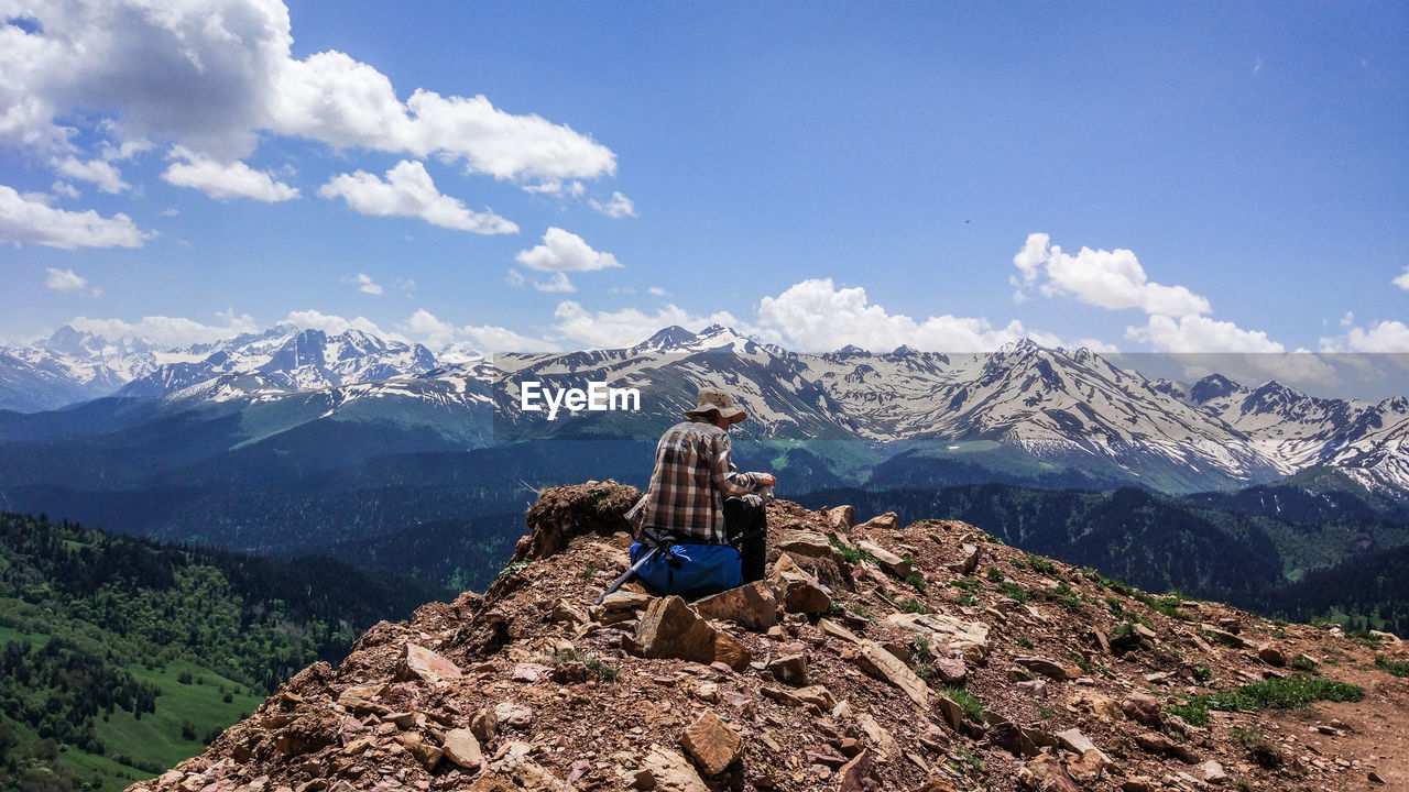 Rear View Of Man Sitting On Rock Against Snowcapped Mountain
