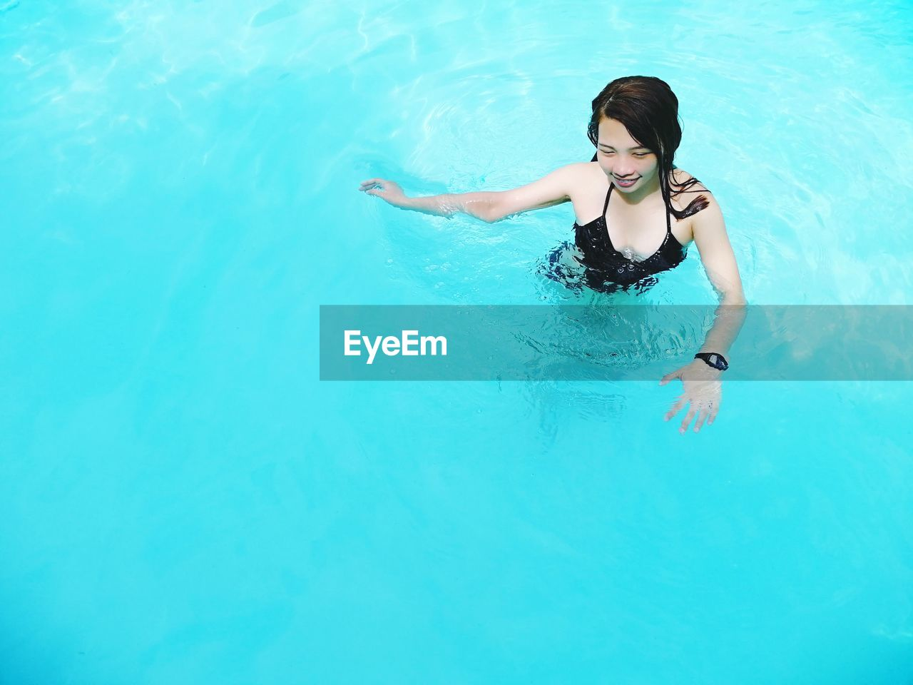 High Angle View Of Smiling Woman Swimming In Pool