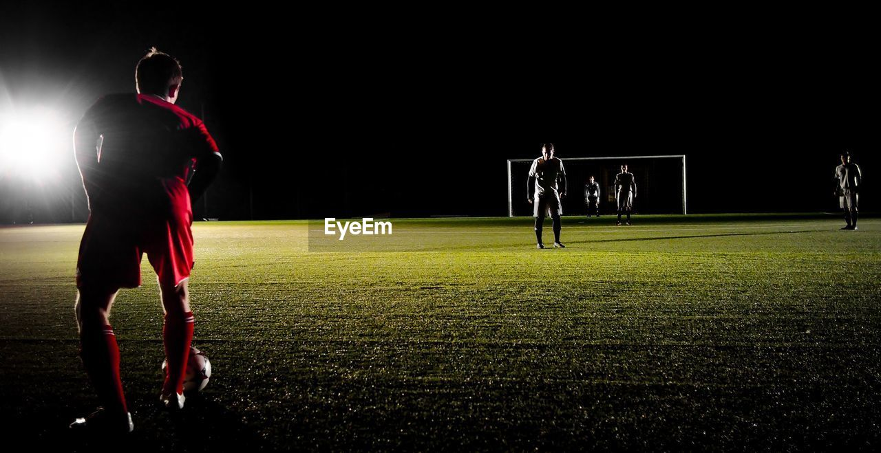 Soccer Playing On Field Against Sky At Night
