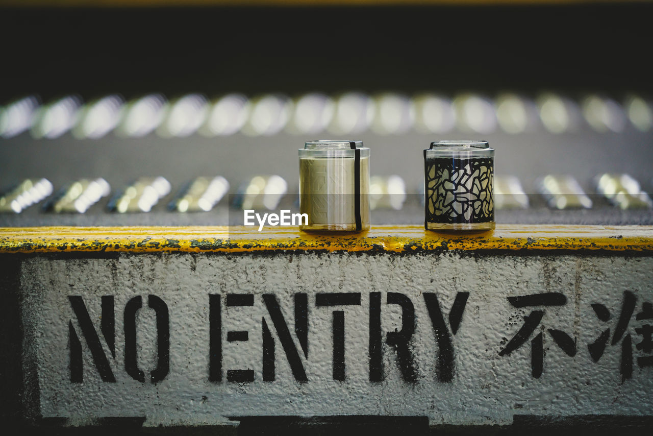 text, communication, western script, capital letter, no people, day, close-up, focus on foreground, sign, metal, outdoors, still life, wall, single word, information, sunlight, architecture, number, container, railing, message