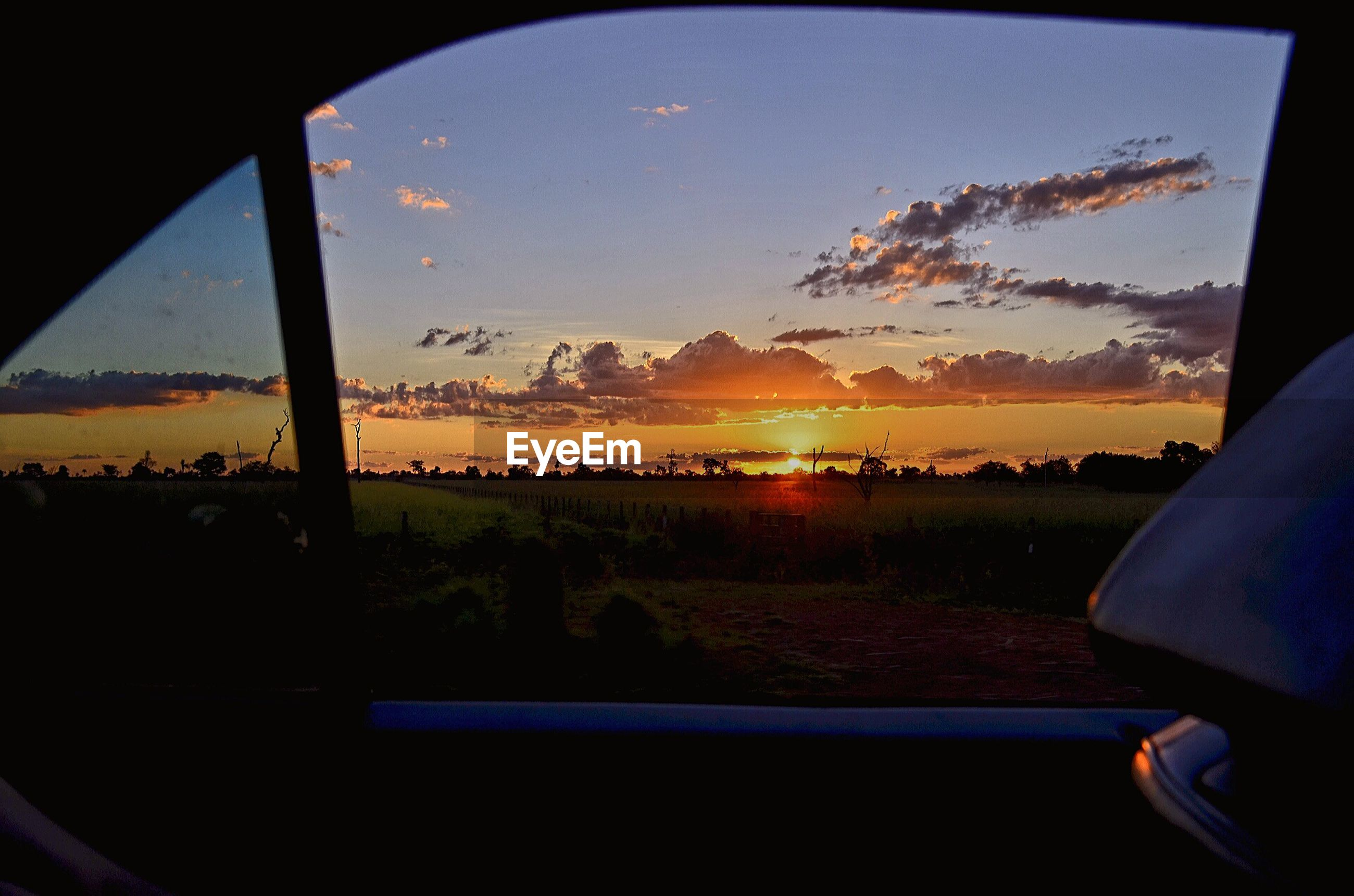 sunset, sky, silhouette, vehicle interior, scenics, window, landscape, sun, tree, transportation, beauty in nature, orange color, glass - material, tranquil scene, transparent, nature, tranquility, mode of transport, car, land vehicle