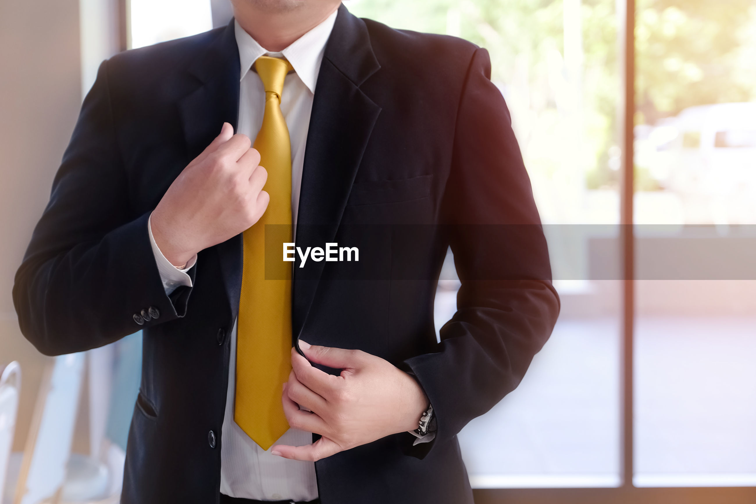 Midsection of businessman holding his blazer in office