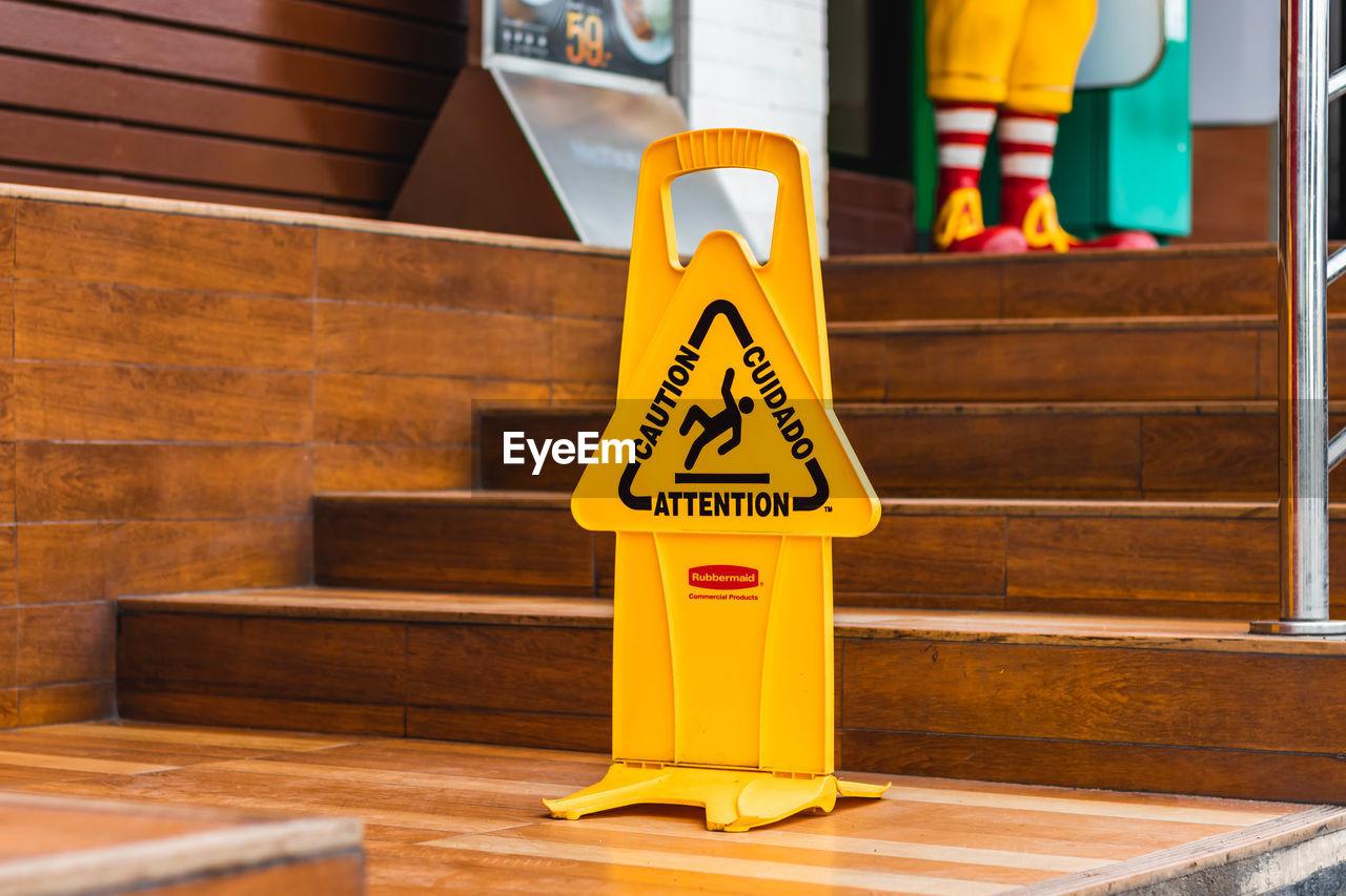 communication, text, yellow, sign, western script, wood - material, indoors, day, incidental people, focus on foreground, representation, human representation, warning sign, non-western script, information, script, architecture, sunlight, warning symbol, message