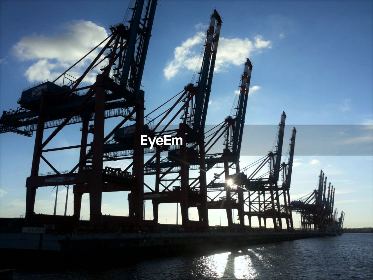 Low angle view of cranes at harbor