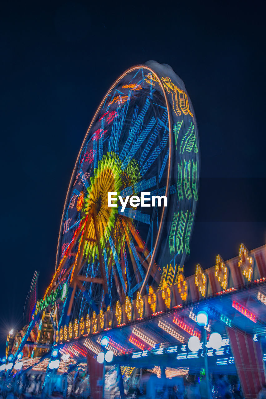 amusement park, amusement park ride, ferris wheel, arts culture and entertainment, illuminated, night, multi colored, sky, no people, carnival, low angle view, outdoors, fairground, nature, traveling carnival, motion, spinning, travel destinations, glowing, clear sky, nightlife