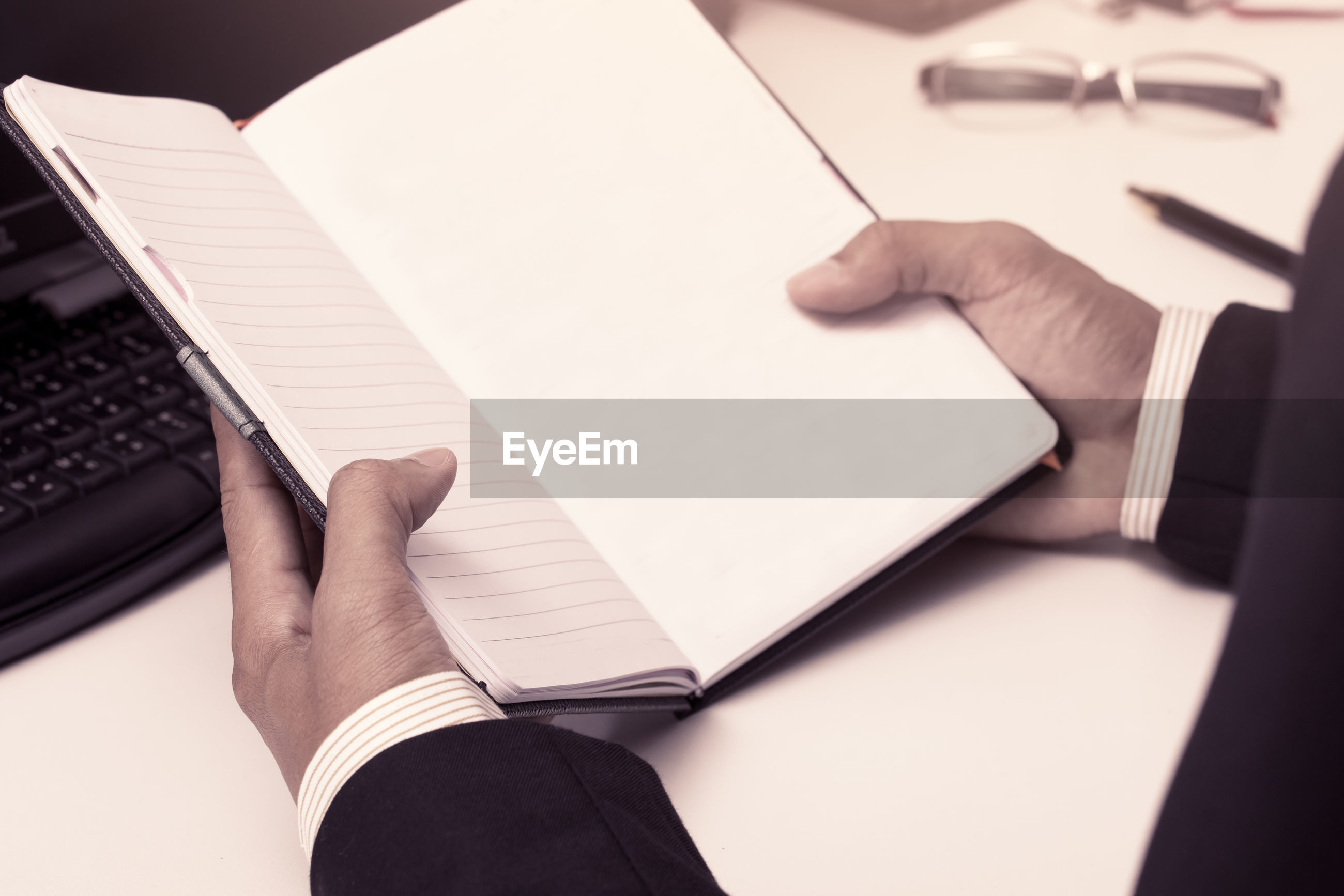 Cropped hand of businessman holding blank diary in office
