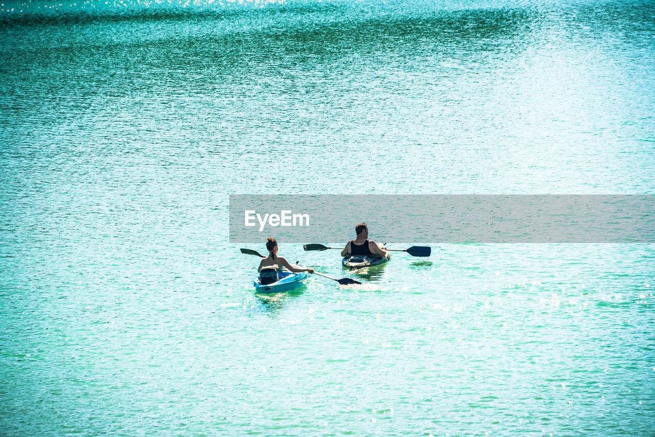 water, waterfront, real people, lifestyles, day, men, nature, leisure activity, nautical vessel, sea, two people, people, high angle view, transportation, togetherness, mode of transportation, women, outdoors, adult, turquoise colored