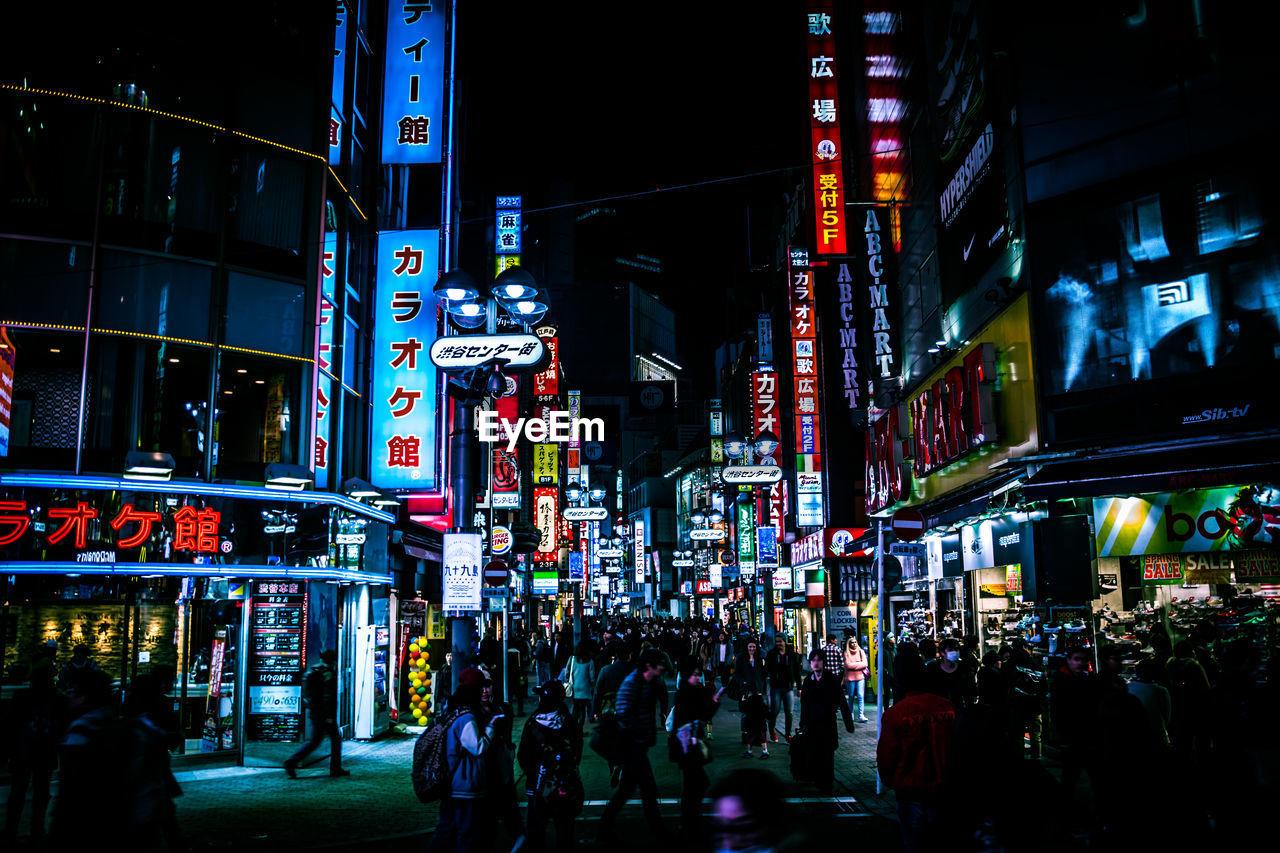 People On Street Amidst Illuminated Billboards On Buildings In City