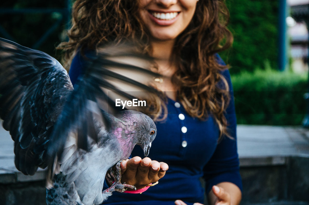 Midsection Of Smiling Woman Feeding Pigeon