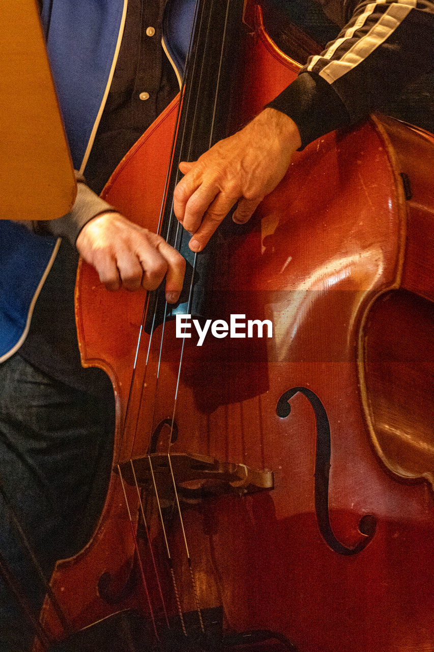 musical instrument, music, musical equipment, arts culture and entertainment, string instrument, artist, skill, musician, one person, real people, men, human hand, playing, hand, midsection, performance, musical instrument string, human body part, holding, entertainment occupation, finger, double bass, bow - musical equipment, stage, human limb