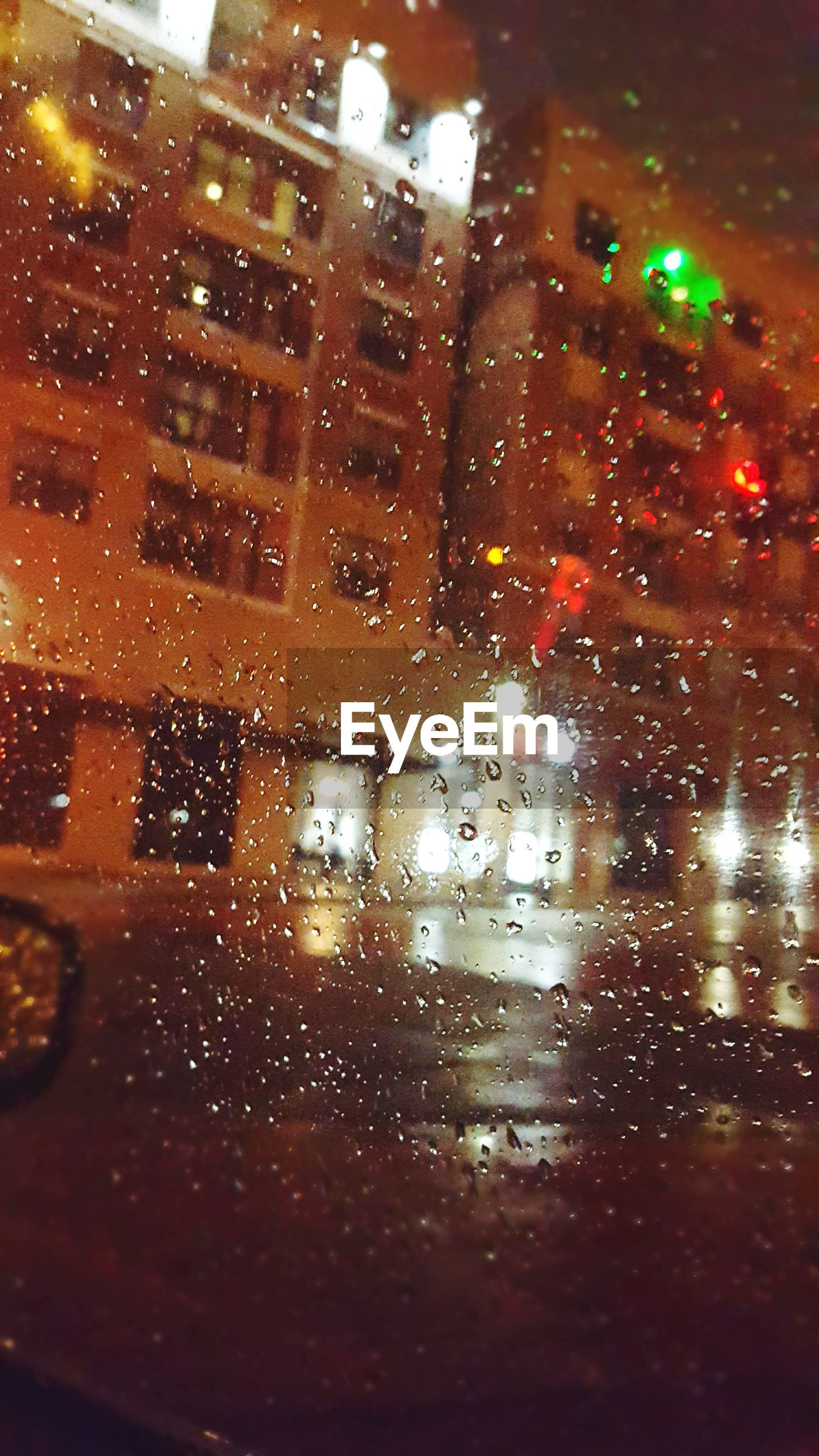 Street and building seen through wet car windshield at night during monsoon