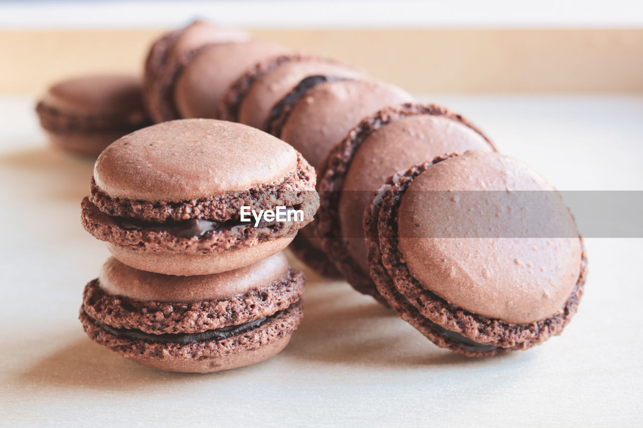 food and drink, food, sweet food, still life, ready-to-eat, indulgence, freshness, temptation, sweet, indoors, baked, close-up, macaroon, dessert, unhealthy eating, table, focus on foreground, no people, brown, stack, snack, french food
