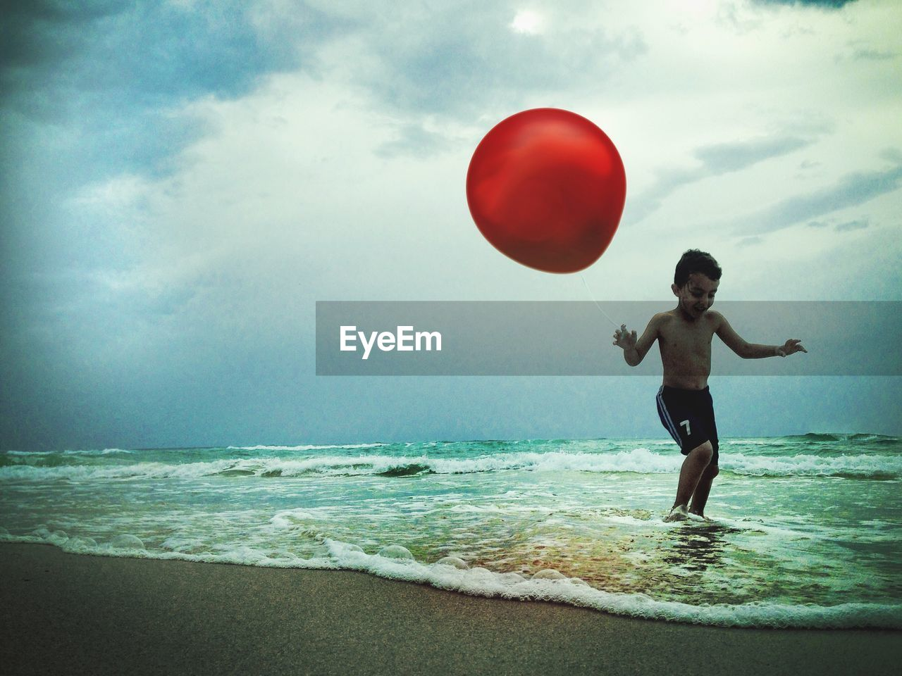 Boy with red helium balloon playing at beach
