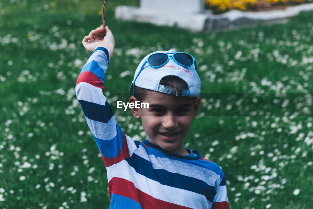 Portrait Of Boy Aiming With Plant On Field