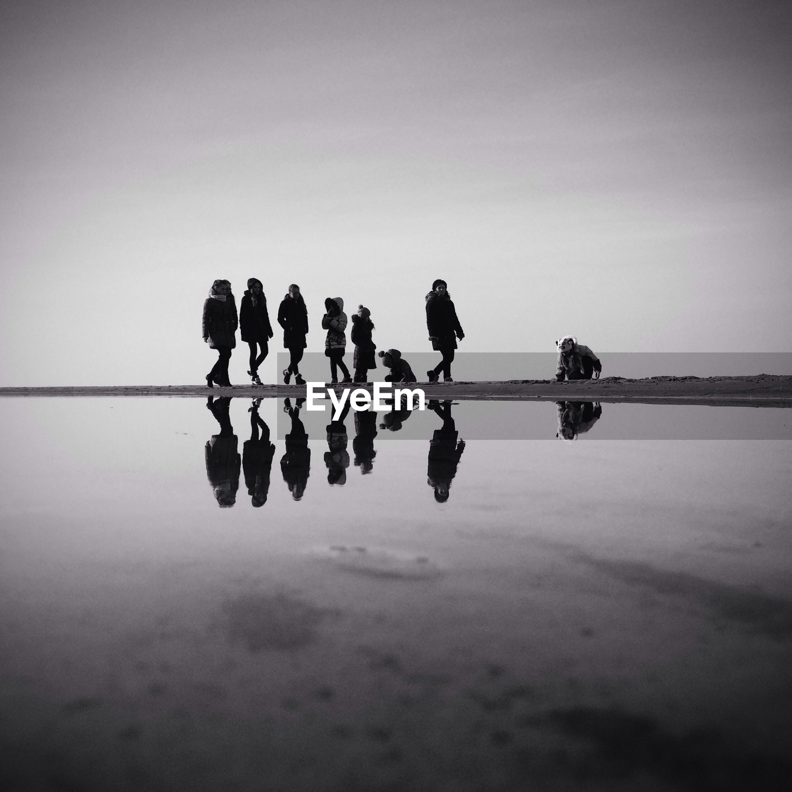 Group of people with reflection on beach