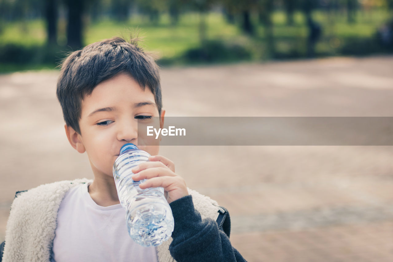Close-Up Of Boy Drinking Water While Standing At Park