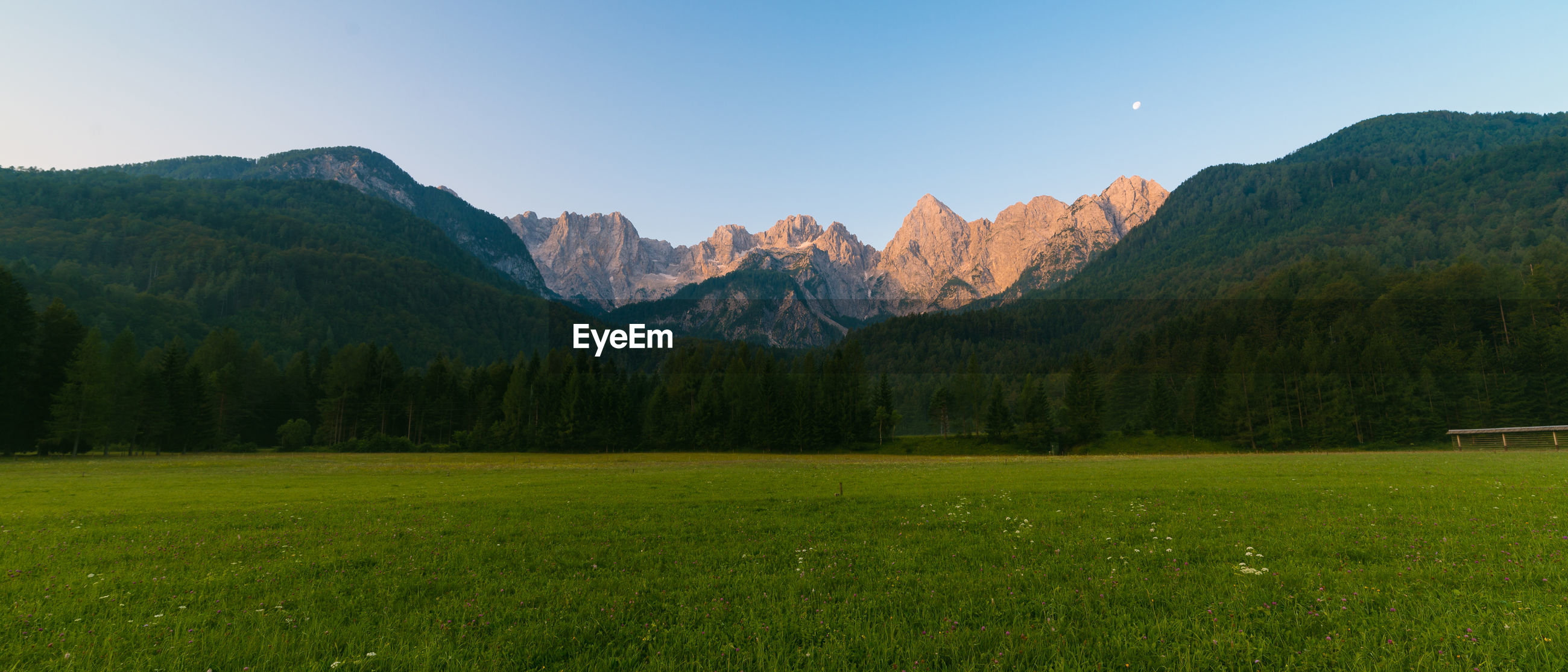 Scenic view of mountains by grassy field against sky