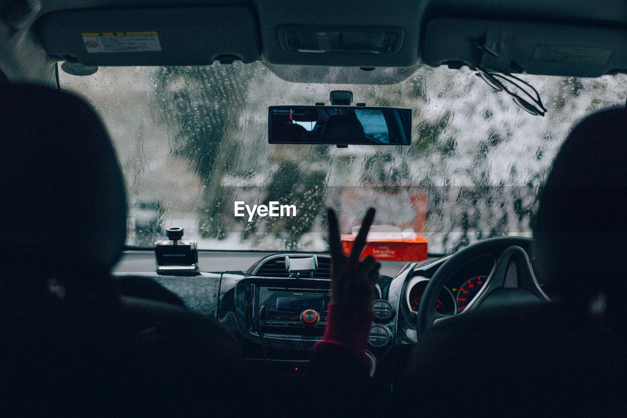 Man gesturing while sitting in car during rainy season
