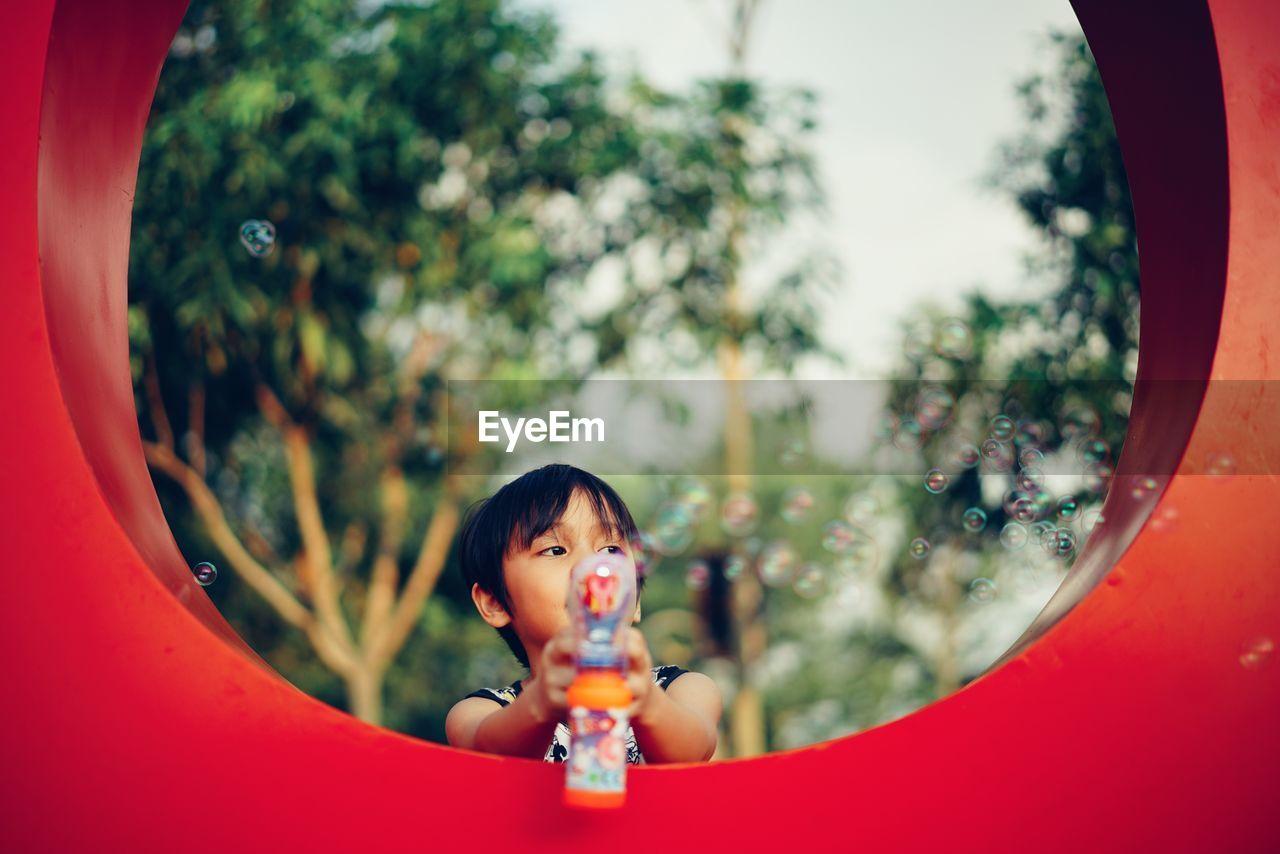 Boy Blowing Bubbles At Park
