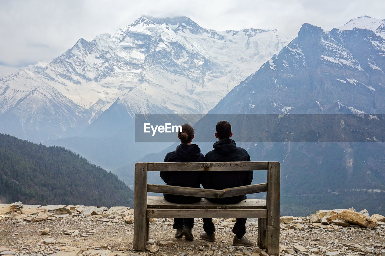 Rear View Of Couple Sitting On Bench Against Snowcapped Mountains