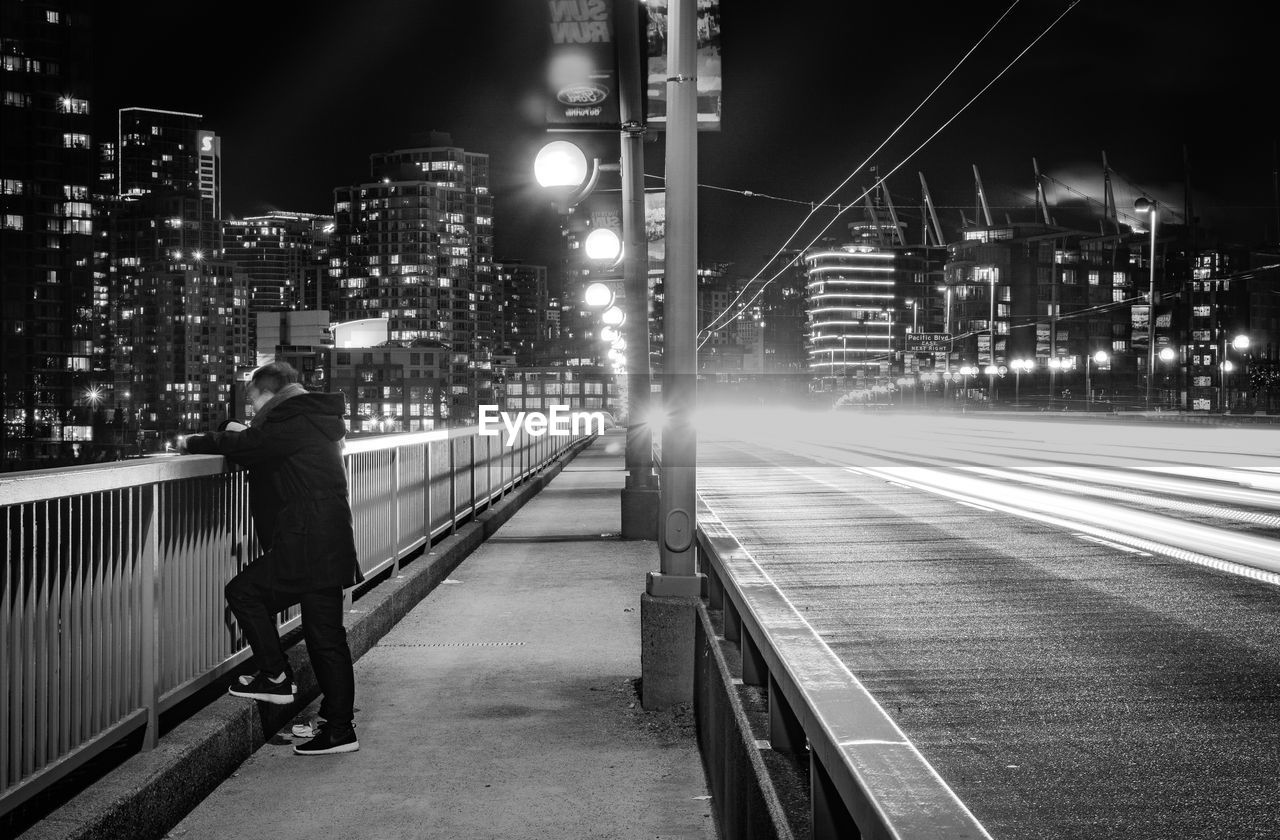 night, illuminated, transportation, one person, real people, city, city life, motion, street light, architecture, built structure, building exterior, outdoors, full length, road, leisure activity, men, lifestyles, sky, adult, people