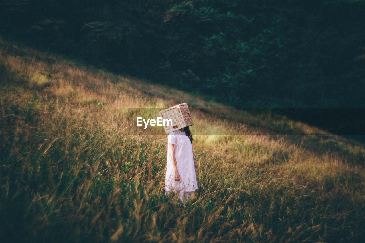 High angle view of woman hiding face with wooden box while standing on field