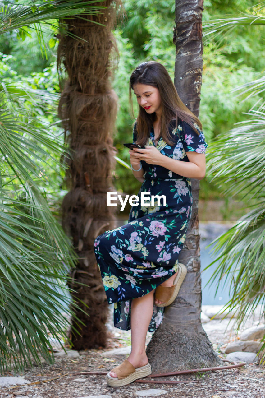 Full length of young woman using mobile phone while standing against trees
