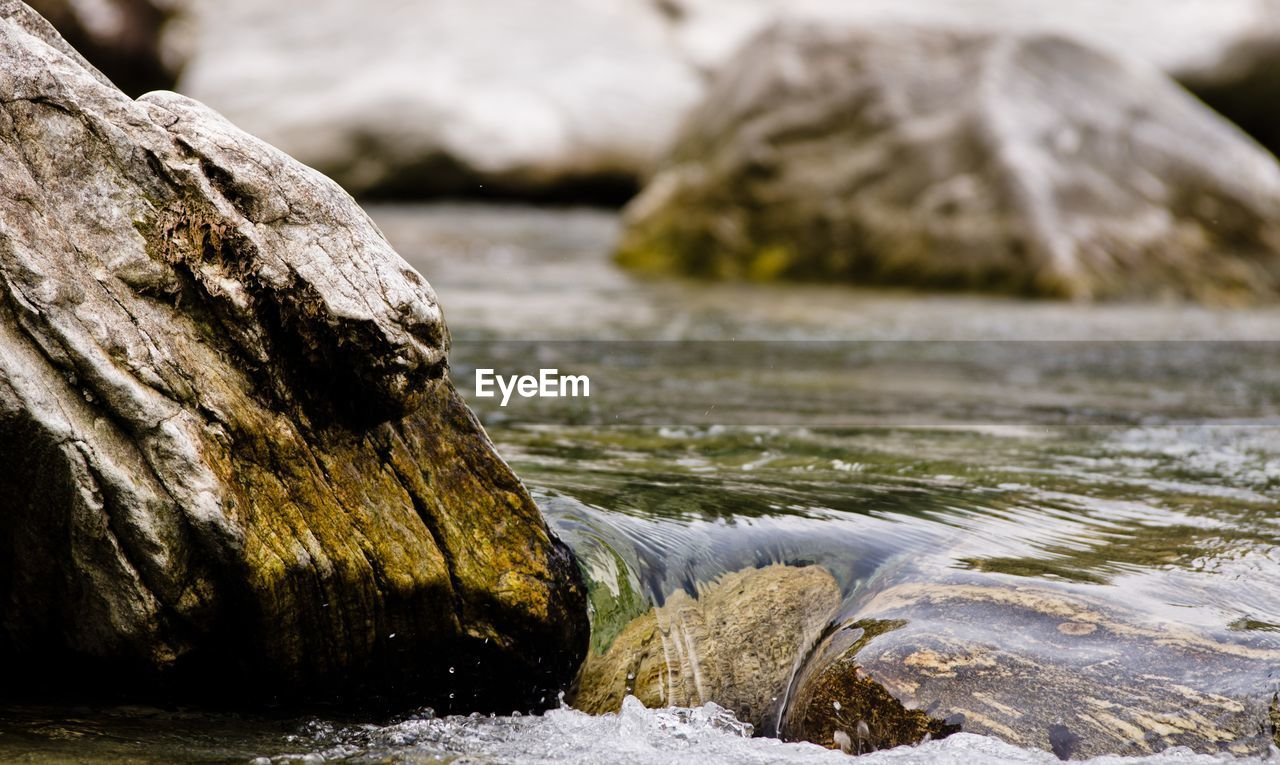 CLOSE-UP OF ROCK IN RIVER