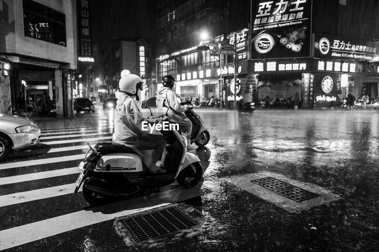 mode of transportation, transportation, city, architecture, land vehicle, illuminated, built structure, building exterior, night, motorcycle, street, real people, sign, men, scooter, motion, communication, road, one person, outdoors, riding, crash helmet